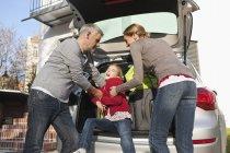 Family loading luggage into car — Stock Photo