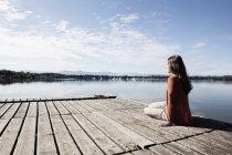 Joven mujer sentada en el muelle - foto de stock