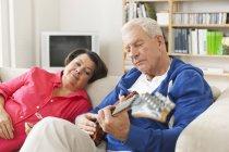 Homme âgé jouant de la guitare électrique sur le canapé, femme assise à côté — Photo de stock
