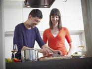 Homme et femme à cuisiner ensemble dans la cuisine — Photo de stock