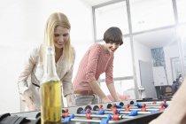 Jovens mulheres jogando futebol de mesa, sorrindo — Fotografia de Stock