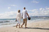 Пожилые супружеские пары, прогулки вдоль пляжа — стоковое фото