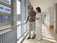 Senior man and caretaker standing in corridor — Stock Photo