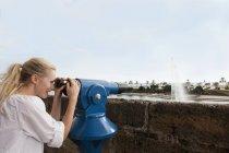 Spagna, Maiorca, Palma, Giovane donna che guarda attraverso il telescopio, sorridente — Foto stock