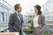 Smiling Business people standing on balcony in office building — Stock Photo