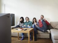 Man and woman watching TV, smiling — Stock Photo