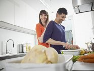 Man and woman cooking together in kitchen — Stock Photo