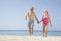 Senior couple walking on beach at Atlantic ocean — Stock Photo