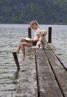 Austria, Teenage girl reading book beside dog on jetty — Stock Photo