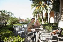 Spain, Mallorca, Palma, Couple sitting at table in cafe, smiling, portrait — Stock Photo