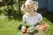 Girl holding vegetables in crate — Stock Photo