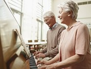 Senior couple playing piano in nursing home — Stock Photo