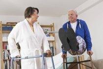 Ältere Frau und Mann spielt mit walking frame — Stockfoto