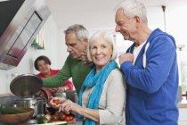 Senior men and women cooking food — Stock Photo