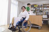 Seniorin sitzt im Rollstuhl eine andere Frau arrangiert Krankenbett — Stockfoto