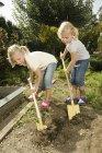 Girls in vegetable garden with shovels — Stock Photo