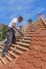 Mitte erwachsener Mann schneidet Dachziegel — Stockfoto