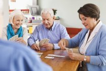 Senior men and women playing cards — Stock Photo