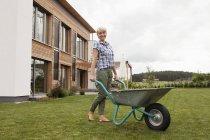 Mature woman with wheelbarrow in garden — Stock Photo