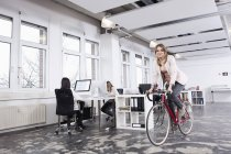 Woman cycling in office while colleagues working — Stock Photo