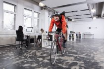 Courier man cycling in office, colleagues working — Stock Photo