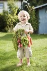 Boy holding carrots and red radish — Stock Photo