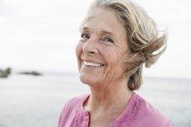 Mulher sênior sorrindo para o oceano Atlântico — Fotografia de Stock
