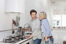 Mature couple preparing food in kitchen — Stock Photo