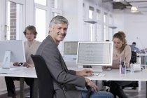 Hombre maduro con colegas que trabajan en segundo plano - foto de stock