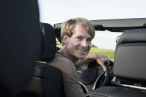 Homme en voiture souriant à la caméra — Photo de stock