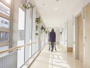 Senior woman with walking frame at corridor in nursing home — Stock Photo