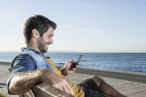 Spain, Mid adult man using smart phone, smiling — Stock Photo