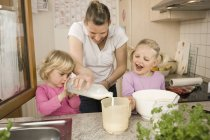 Mother and daughter pouring milk — Stock Photo