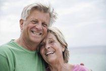 Улыбающаяся старшая пара, стоящая лицом к лицу на пляже — стоковое фото