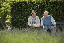 Due vecchi che usano tablet nel parco — Foto stock