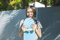 Skate boarder femelle tenant skateboard — Photo de stock