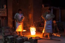 Germany, Munich, Foundry worker pouring hot metal into cast — Stock Photo