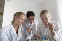 Teenage girls and young woman having a chemical experiment — Stock Photo