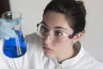 Lab technician examining liquid — Stock Photo