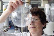 Chemikerin blickt auf Fläschchen — Stockfoto