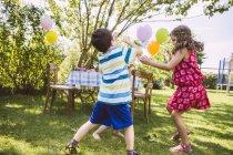 I bambini che cercano di catturare bolle di sapone in giardino — Foto stock