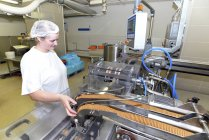 Germany, Saxony-Anhalt, woman controlling cookies on production line in a baking factory — Stock Photo