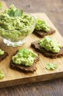 Pumpernickel slices with a pea and walnut spread on a cutting board — Stock Photo