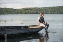 Hombre con cerveza en bote de remos en el lago Laach, Renania-Palatinado, Alemania - foto de stock