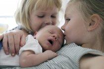 Deux petites filles baiser frère nouveau-né — Photo de stock