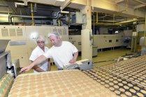 Два работника на производственной линии с печеньем на хлебопекарной фабрике — стоковое фото