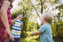 Bambini che saltano sapone bubbbles nel giardino — Foto stock