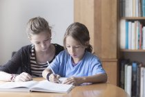 Sister helping her little brother by doing his homework — Stock Photo