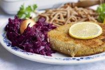 Schnitzel de tempeh con spaetzle de repollo y trigo rojo - foto de stock