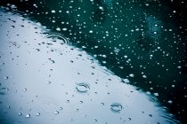 Raindrops falling on puddle, partial view — Stock Photo